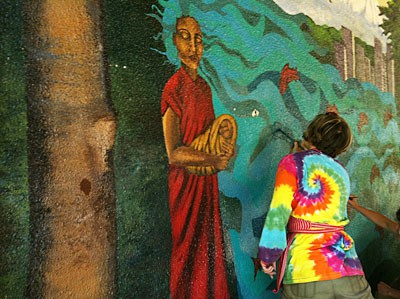 A community member repaints the Wilshire Park mural by Anna Garibay (Courtesy of RACC)
