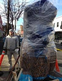 "Artist David Laubenthal (at left) stands with the ""wrapped"" sculpture to be unveiled on December 14th at NE Alberta street and 18th."
