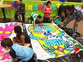 Rodolfo Serna (right) leads young artists from the Boys and Girls Club as they create work for their Día de los Muertos installation at the Portland building.