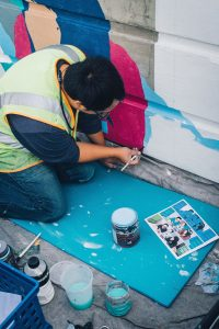 alex chiu kneeling at the ground, paintbrush in hand, painting his mural at trimet.