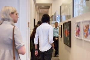 Latinidades attendees walk down the HMC office hall to view featured artwork