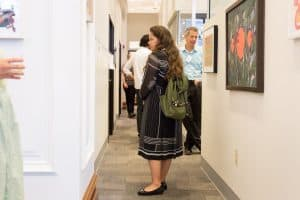Show attendee viewing the feature artist artwork in the Hispanic Metropolitan Chamber
