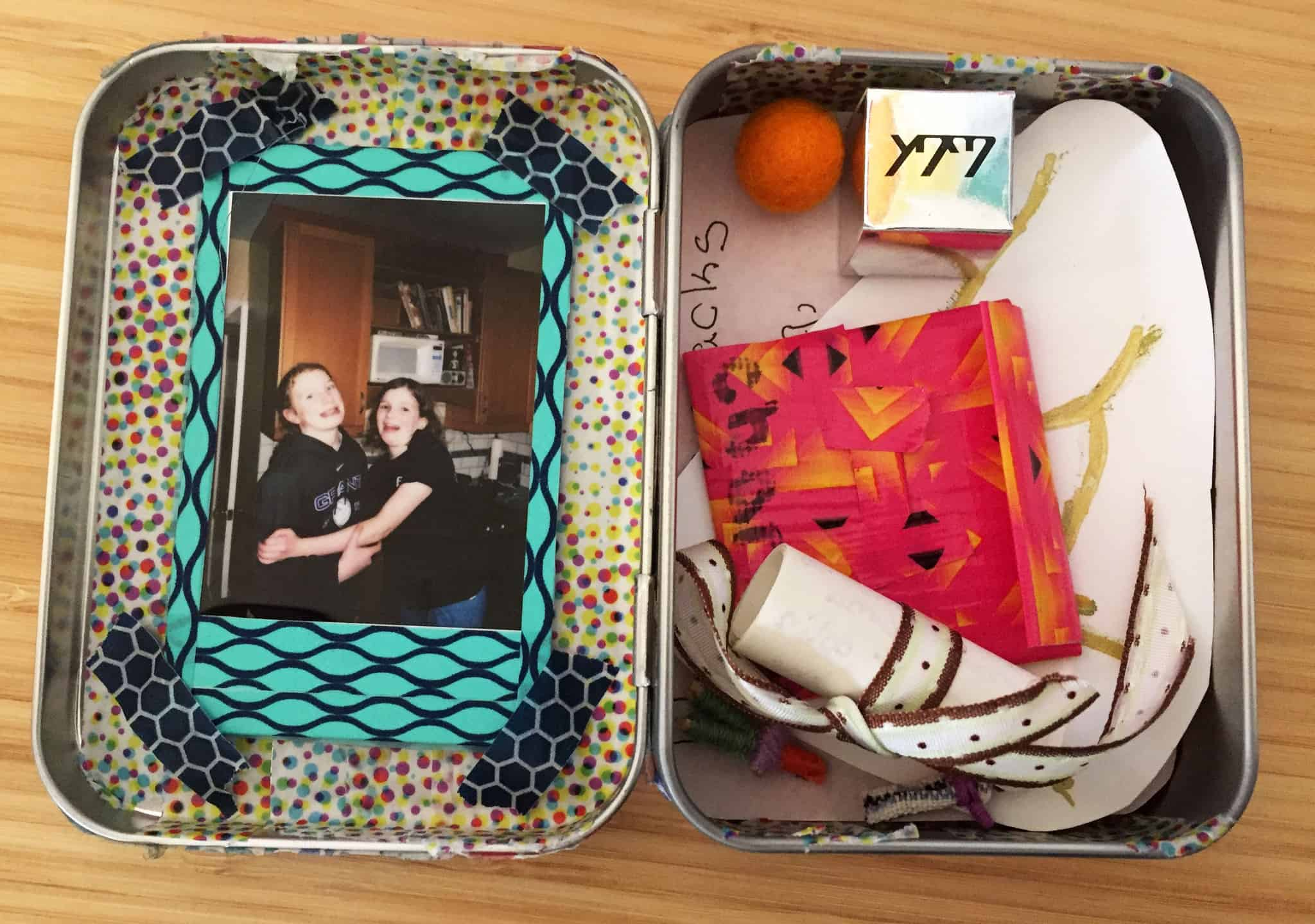 Metal tin open, face up, with contents inside of it. On the left there's a photo of two youth smiling at the camera. On the right there are miscellaneous items including a red ball, small box, and paper.