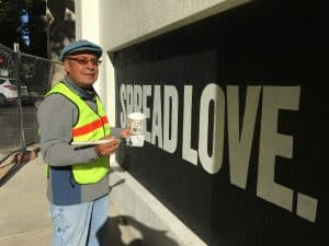 Artist Jose Solís stands in front of a mural with the words spread love in white letters on a black background. He is holding a paintbrush and container with paint.