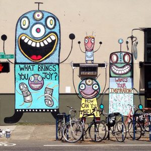 A street mural with whimsical robotic characters in front of a bike rack.