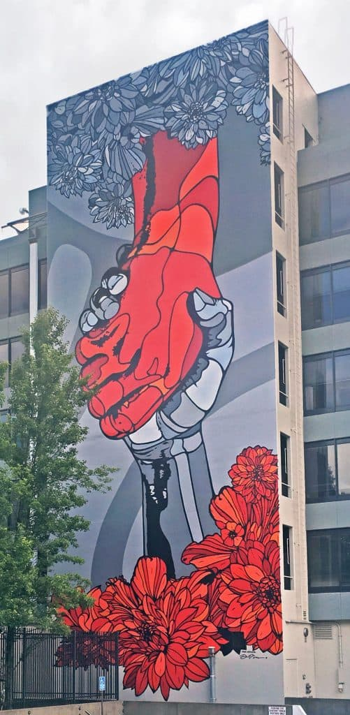 Image of a large building mural with two hands clasped, one red and one grey, emerging from the flowers.