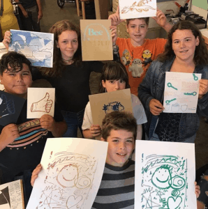 A group of young art students hold up their colorful prints.