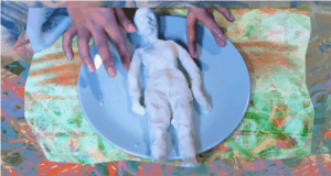 Image from video shows hands on a blue plate holding a clay figure of a person