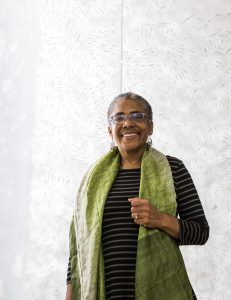 Artist Barbara Earl Thomas stands in front of a intricate steel cut panel. She has short-cropped hair and wears a chartruse colored scarf draped over her shoulders against a black shirt.